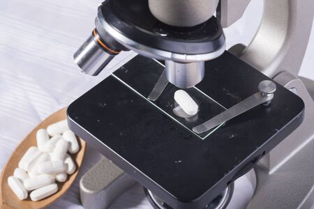 a tablet blister: White pill on microscope Stock Photo