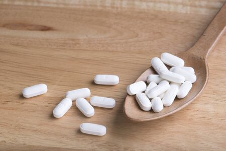 a tablet blister: White pill on wood spoon and on wood table Stock Photo