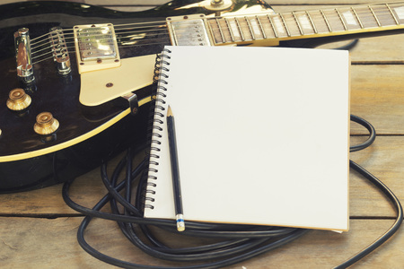 electricguitar with notepad on wood table