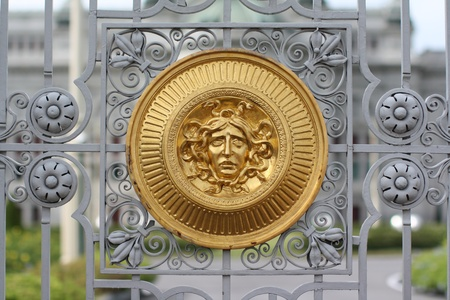 Golgen medusa head at fence of palace Stock Photo