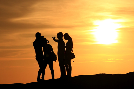 Silhouette of people in the evening at the beach. photo