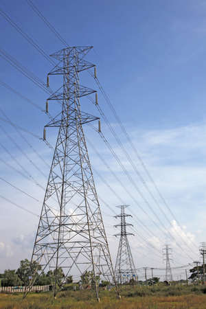 high voltage power pylons on sky blue