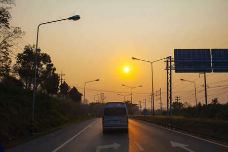 Asphalt road with oncoming truck in sunset