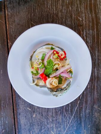 Spicy oyster salad on white plate