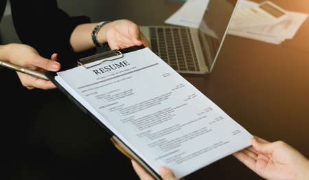 A young woman sends a resume to a human resource manager to consider the application. The human resource manager makes hiring decisions. Interview concept.