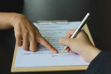 A woman signed a document to become a new employee of the office. Contract and job application concepts Zdjęcie Seryjne