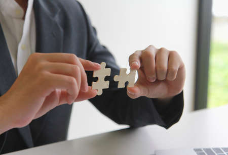 A man uses both hands to try to connect the two jigsaw puzzles together. symbol of association and connection. support and help concept. Banque d'images