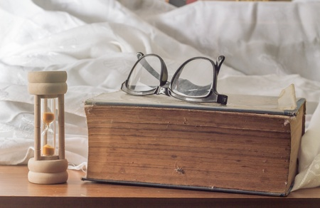 Aged book with eyeglass and sand glass