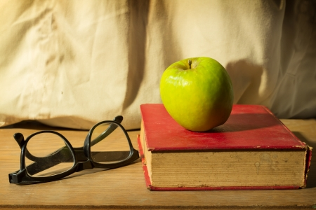 Antique book with eyeglasses and green apple  photo