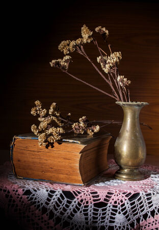 Still life dry flowers in metal vase with antique book  photo