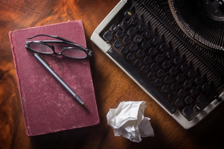 Old typewriter with book,pen and eyeglasses photo
