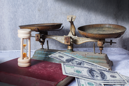 Scale with hourglass,book and money  photo