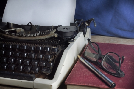Typewriter with antique book and eyeglasses
