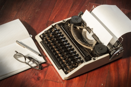 Typewriter with book and eyeglasses Stock Photo