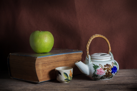 Still life book with apple and tea kit  photo