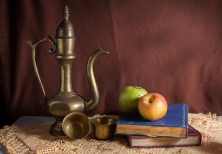 Still life meatl jug with apples and books  photo