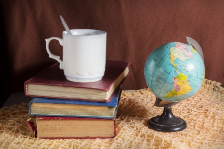 Still life stack books with coffee cup and globe  photo