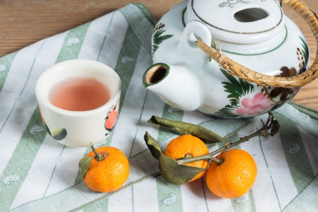 Tea pot and cup with small orange  photo