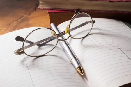 Reading table,Eyeglasses and pen on book  photo