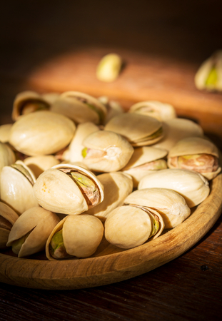 plate of food: Pistachios nut in wood plate,food background  Stock Photo