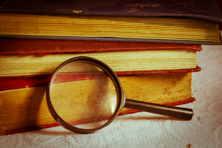 Magnifier with books,retro style color  photo