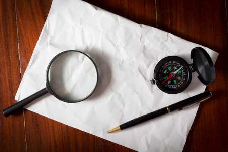 Compass with magnifier and pen on paper. photo