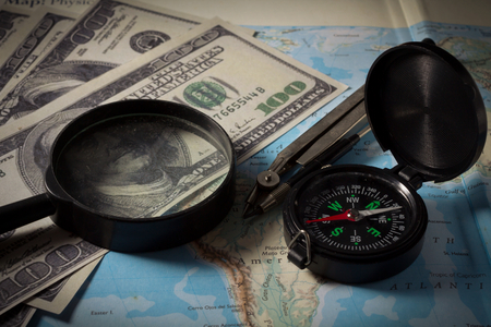 Compass with magnifier and money on map,business concept. photo