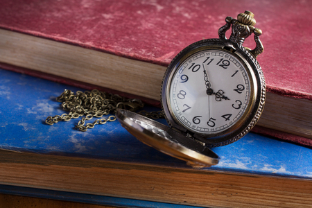 Pocket watch with antique book,still life.