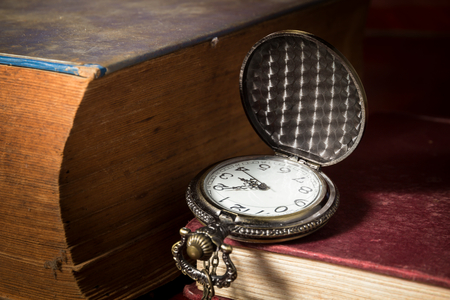 ancient pass: Still life pocket watch with antique book