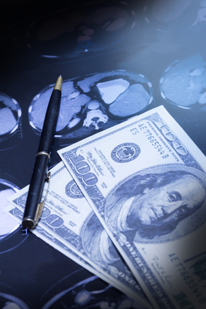 paid medicine: Pen and money on CT-scan flim. Stock Photo