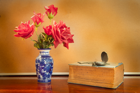 Still life artificial rose in vase with watch and book. photo