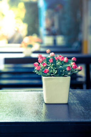 Artificial flowers on wood table,vintage color.