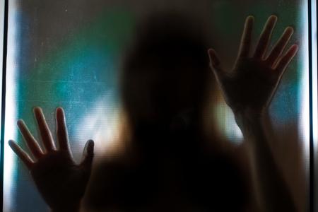 Schaduw vrouw achter transparante glas. Stockfoto