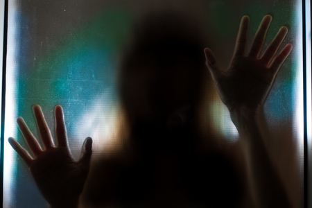 upset woman: Woman shadow behind translucent glass. Stock Photo