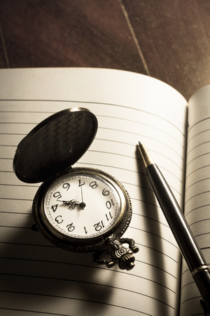 pocket watch: Still life Pocket watch and pen on book. Stock Photo