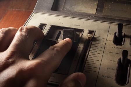 fader: Human hand controlling radio sound,old equipment. Stock Photo