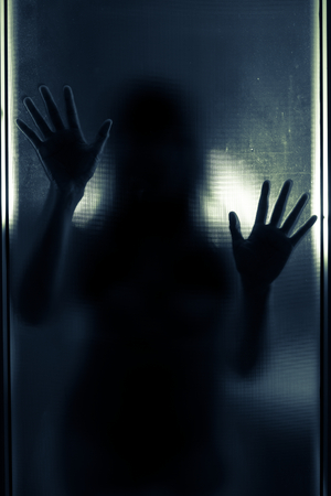 Woman shadow behind translucent mirror,blue tone color filtered. Stock Photo