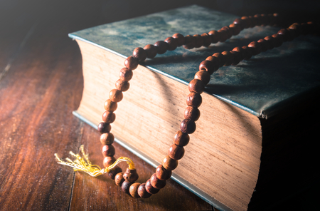 Vintage color filtered of Necklace on book,religion background.