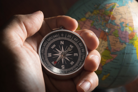 map compass: Compass in human hand with globe,travel concept. Stock Photo