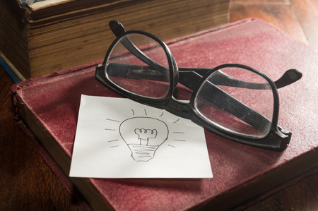 Still life Eyeglasses and book with idea note paper. photo
