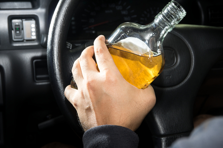 Whiskey in hand and driving,social problem concept. photo