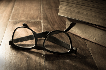 Sepia filtered eyeglasses with antique books,still life.