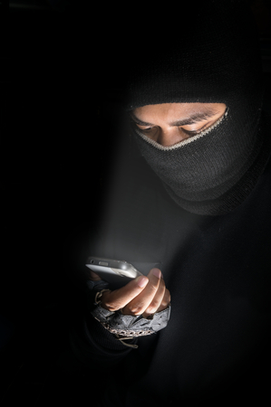 Robber man hacking by smart-phone,hacker concept. photo