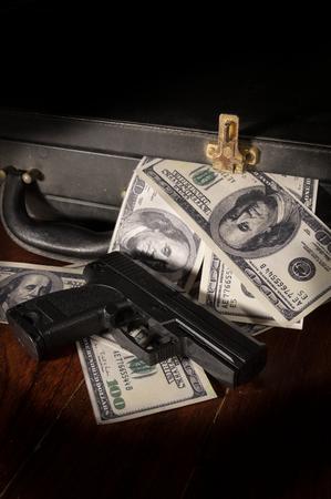 gangster with gun: Gun and dollar bill in briefcase,crime concept. Stock Photo
