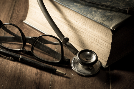 instrumental medico: Estetoscopio con gafas, la pluma y el libro antiguo. Foto de archivo