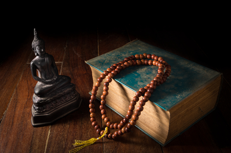 Buddha statue with necklace and antique book,still life. Stock Photo