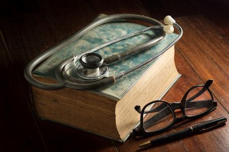 estetoscopio: Estetoscopio con gafas, la pluma y el libro antiguo, la naturaleza muerta. Foto de archivo
