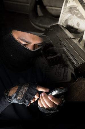 cyber terrorism: Robber man use smart phone with gun and money on background,crime concept.