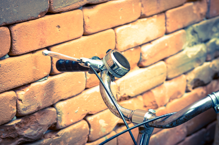 gripping bars: Vintage color filtered of Bicycle Handlebar with bricks wall. Stock Photo