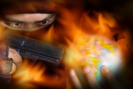 Terrorist put a gun to globe with flame screen,violence concept.